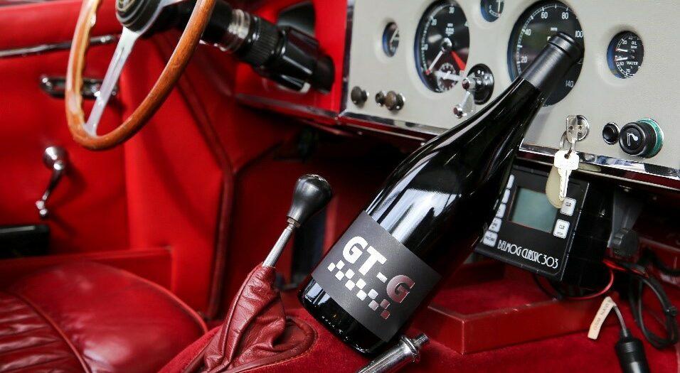 Bottle red wine GT-Grenache on top of the dashboard of a car LePlan-Vermeersch